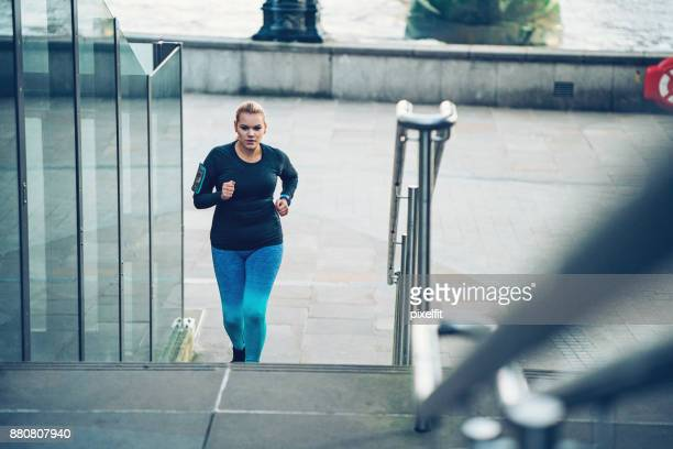 Young overweight woman running outdoors in the city