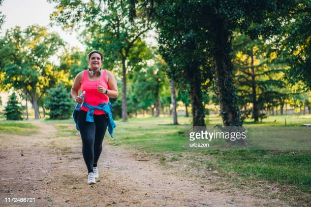 young overweight woman running - big fat women stock pictures, royalty-free photos & images