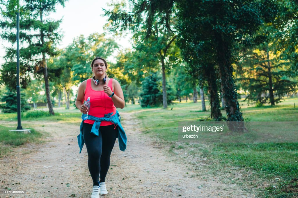 Young overweight woman running : Stock Photo