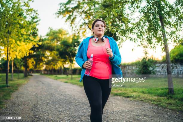 young overweight woman running - relaxation exercise stock pictures, royalty-free photos & images