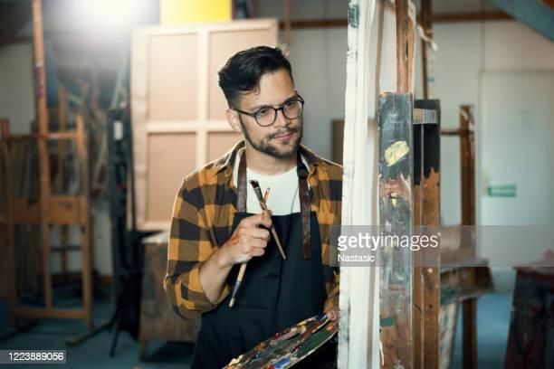 junger maler hält eine farbpalette und überlegt über ein gemälde - staffelei stock-fotos und bilder