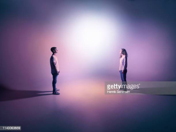 young pair looking at light - face to face stock pictures, royalty-free photos & images