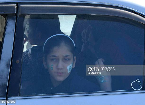 A young Pakistan girl looks out the car window on arrival to attend a ceremony to mark the first anniversary of the school massacre which left more...