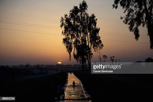 A young Pakistani boy internally displaced swims in a canal at the Yar Hussain UNHCR camp in Chota Lahore on July 6 2009 in Swabi district Pakistan...