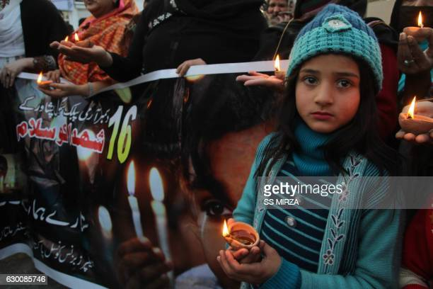 A young Pakistani child joins residents holding lighted lamps during a ceremony in Multan on December 16 as they pay tribute to victims on the second...