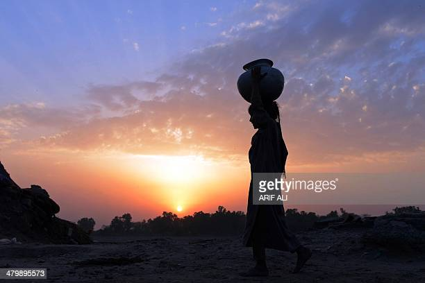 A young Pakistani girl carries a water pot over her head as she heads for home during sunset on the outskirts of Lahore on March 21 on the eve of...