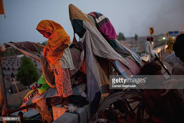 A young Pakistani girl displaced from her home by flooding watches her family members prepare dinner as she stands on her families belongings in...
