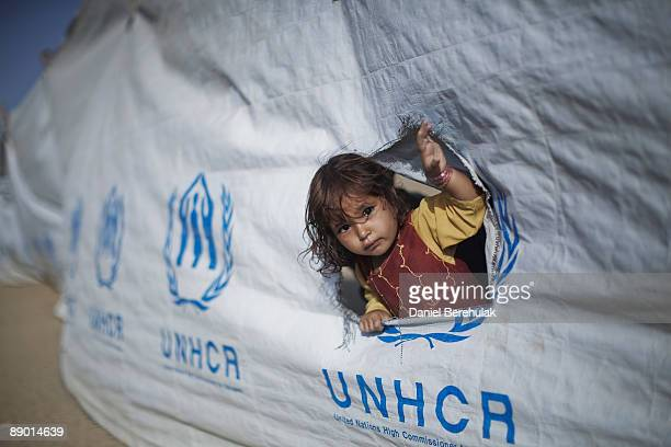 Young Pakistani girl, internally displaced from Swat, looks out from a hole in a fence as her family wait to board a bus before departing from the...