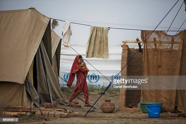 A young Pakistani girl internally displaced from Swatcaries her younger sister at the Yar Hussain UNHCR camp in Chota Lahore on July 12 2009 in Swabi...