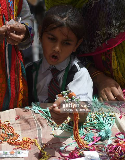 A young Pakistani Hindu child looks at rakhi or sacred threads for sale on the occasion of the Hindu festival Raksha Bandhan at a roadside stall in...