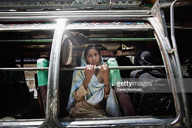 A young Pakistani IDP looks out from the window of a bus as she returns to her village of Sultanwas on July 16 2009 near Dagar in Buner Pakistan...