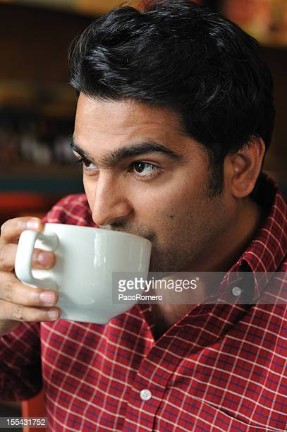 young pakistani man having coffee - handsome pakistani men stock photos and pictures