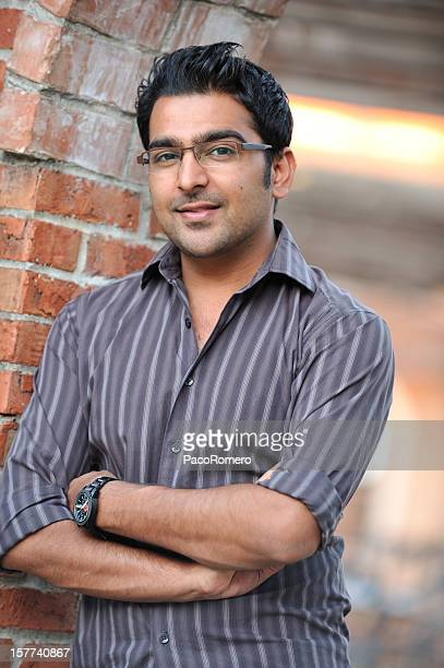 young pakistani man with arms crossed - handsome pakistani men stock photos and pictures