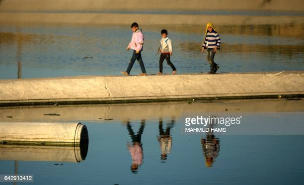 TOPSHOT Young Palestinian boys walk over a mini cement bridge in Beit Lahia in the northern Gaza Strip on February 19 2017 / AFP / MAHMUD HAMS