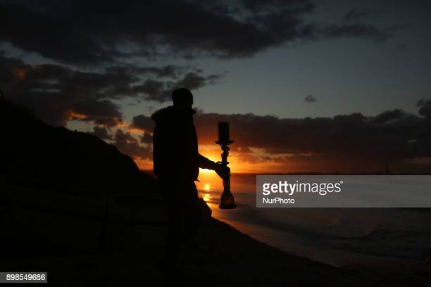 A young Palestinian carry water pipe on the beach at sunset in Gaza City on 25 December 2017