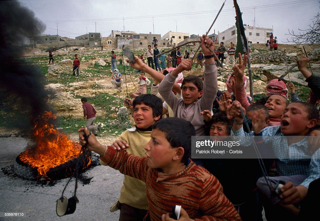Young Palestinian demonstrators burn tires in the street and throw stones at Israeli soldiers during an uprising. Violence broke out after rebel Israeli and Palestinian fighters protested in the disputed territory of West Bank during the first Intifada.
