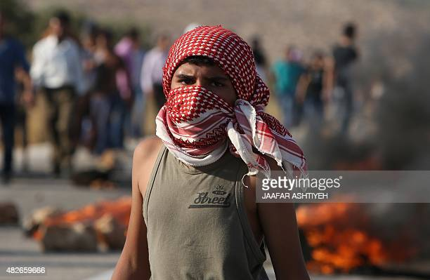 A young Palestinian looks on during clashes with Israeli security forces on a street leading to Duma village on August 1 following a demonstration in...