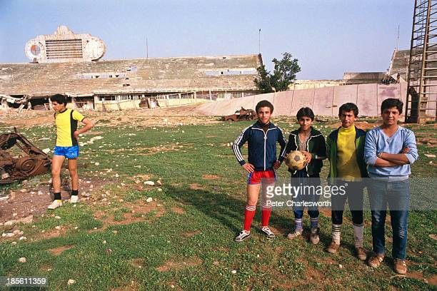 Young Palestinian men and boys play football in the 'city sportif' National stadium which was heavily damaged by Israeli bombardements during the...