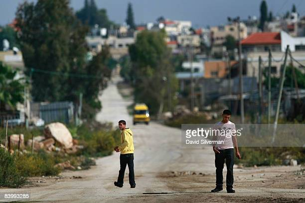 Young Palestinian men walk down what was once a major road from Israel into the West Bank until the Jewish State built it's separation barrier and...