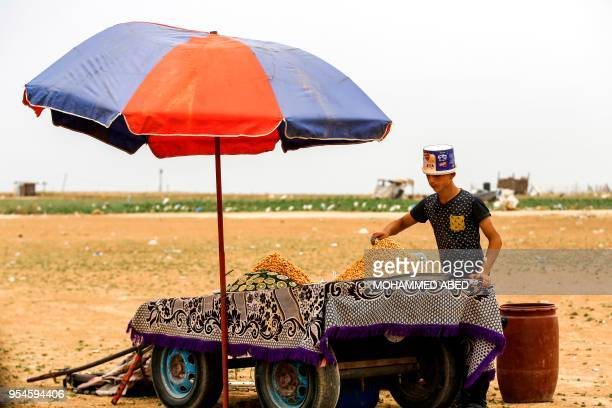 Young Palestinian peddlar sells boiled lupine seeds on a cart while wearing a plastic Feta cheese container for protection near a demonstration east...