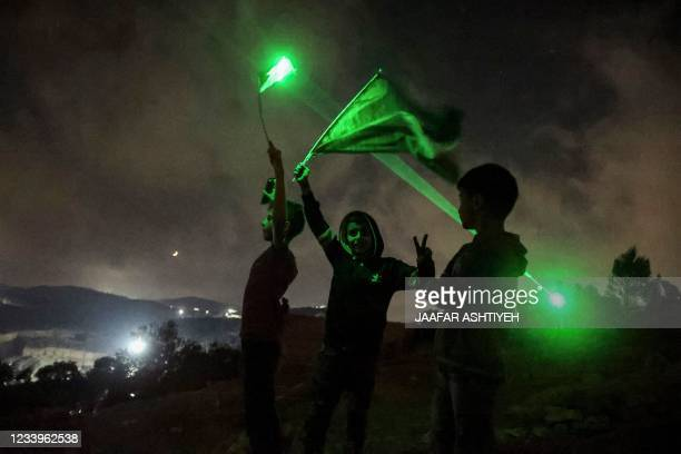 Young Palestinian protesters use laser torches during a demonstration against the Israeli settlers' outpost of Eviatar, in the town of Beita, near...