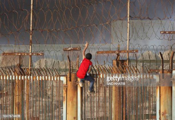 TOPSHOT A young Palestinian protestor climbs a fence during a demonstration on the beach near the maritime border with Israel in the northern Gaza...