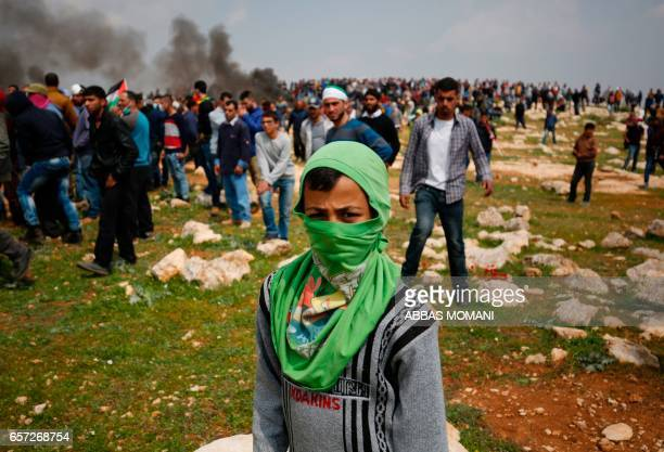 TOPSHOT A young Palestinian protestor poses for a photo during clashes with Israeli security forces following a demonstration against Jewish...