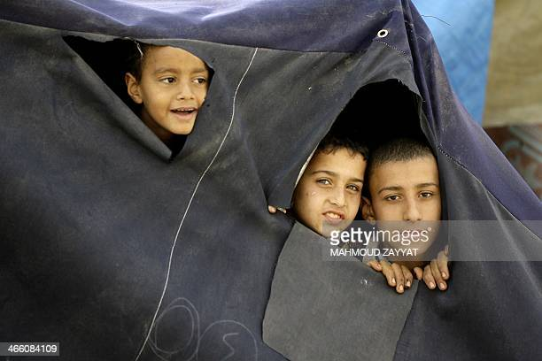 Young Palestinian refugees who fled the Yarmuk refugee camp in Syria where they were previously residing due to the ongoing conflict peer through...