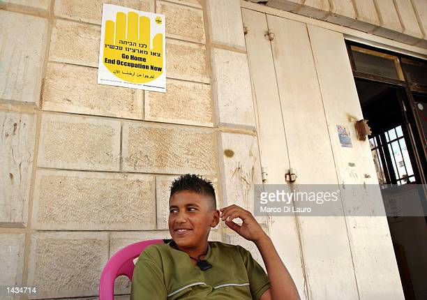 A young Palestinian sits under a poster that reads Go Home End Occupation Now next to the entrance of a grocery shop that is open despite the curfew...