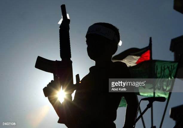 Young Palestinian supporter of The Islamic Resistance Movement holds a fake machinegun while attending a rally to demand the release of Palestinian...