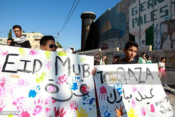Young Palestinians hold placards reading 'Eid Mubarak to Gaza' during a demonstration in solidarity with the children killed in the ongoing Israeli...