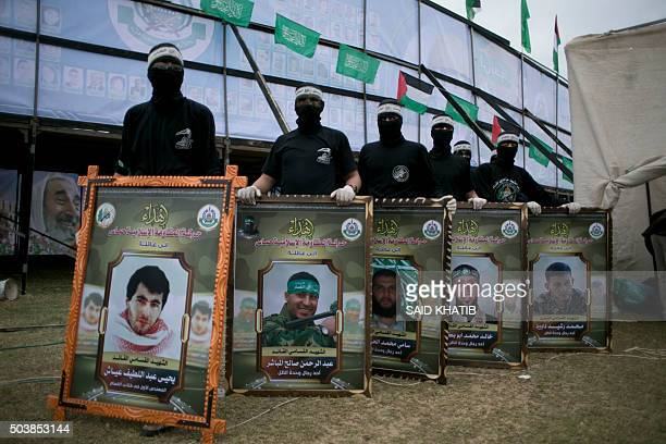 Young Palestinians loyal to the Hamas movement hold portraits of dead Hamas militants who the armed wing said participated in imprisoning Israeli...