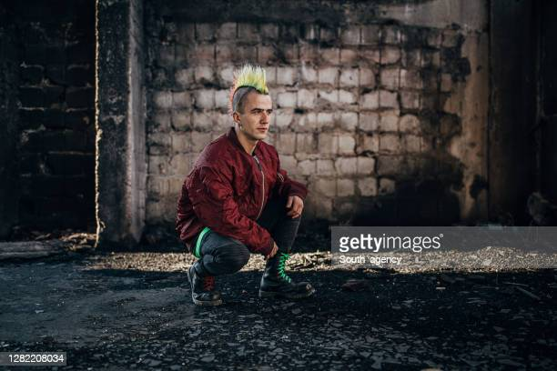 young pank man with colorful coiffure kneeling in abandoned warehouse - bomber jacket stock pictures, royalty-free photos & images