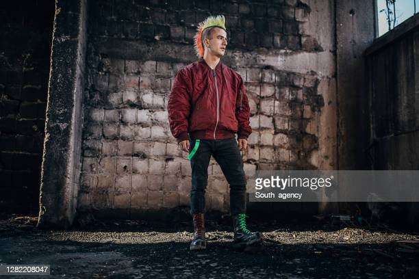 young pank man with colorful coiffure standing in abandoned warehouse - bomber jacket stock pictures, royalty-free photos & images