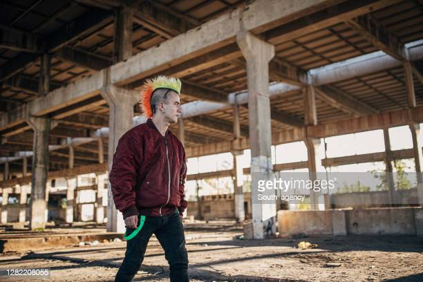 young pank man with colorful coiffure walking in abandoned warehouse - bomber jacket stock pictures, royalty-free photos & images