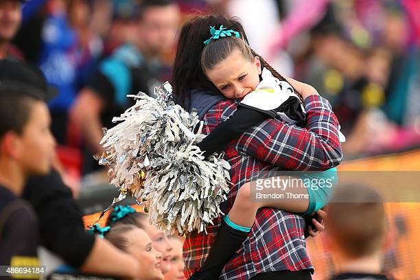 A young Panthers cheergirl shows signs of distress after Panthers and Knights players fight during the round 26 NRL match between the Penrith...