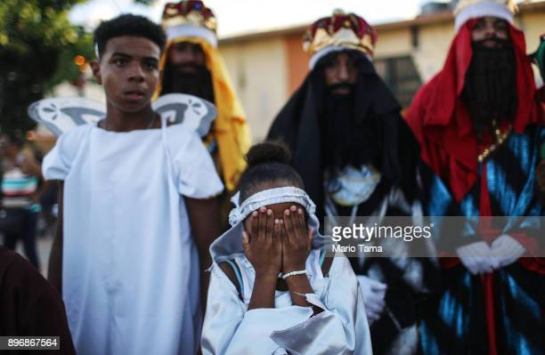 A young parader covers her face at the end a school Christmas parade on December 21 2017 in Loiza Puerto Rico The parade mixed traditional Catholic...