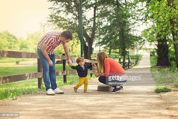 Young parents and their baby boy learning to walk