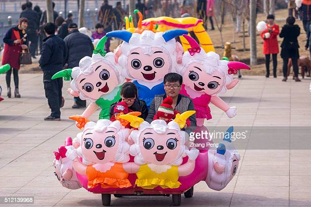 Young parents and their twin babies drive in weird plastic toy cars decorated of all kinds of copycat cartoon characters domestic and abroad which...