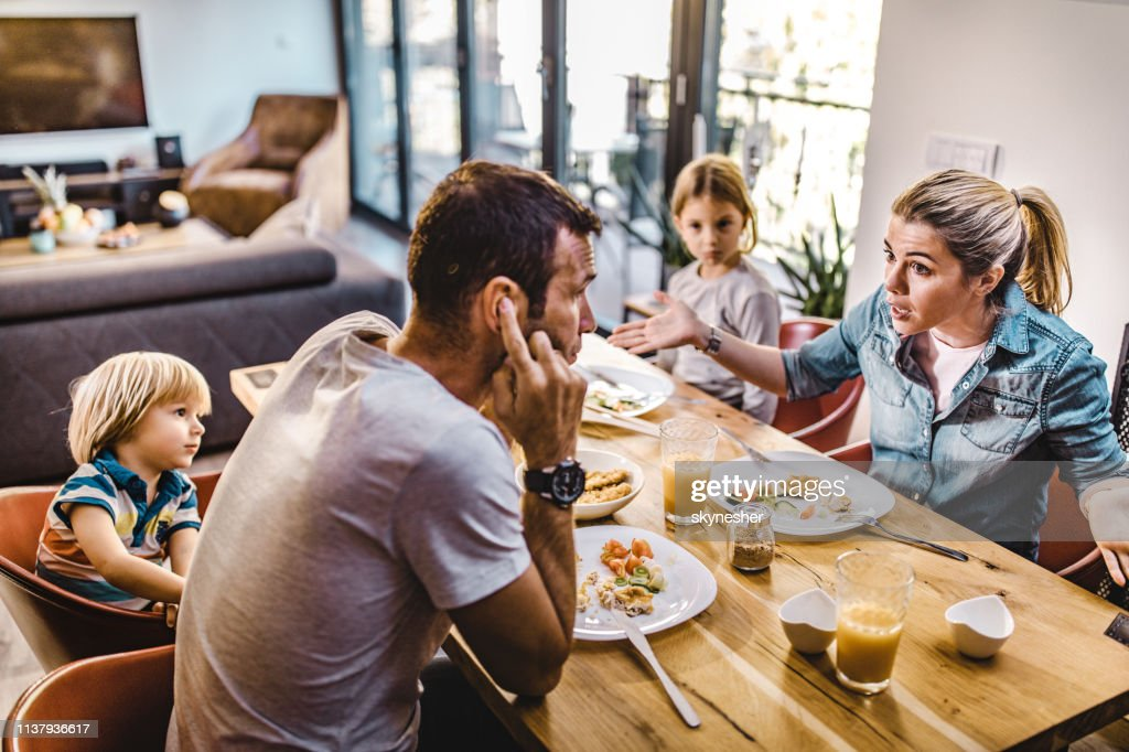 Young parents arguing while having lunch with their kids at home. : Stock Photo