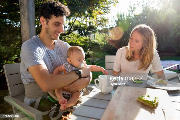 Young parents eat out in a garden with their baby boy