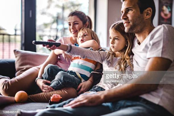 young parents enjoying with their small kids on sofa while watching tv together. - watching tv stock pictures, royalty-free photos & images