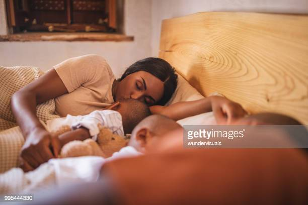Young parents napping in bed with little children