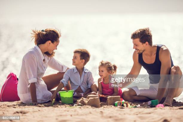 Young parents playing in sand with their son and daughter.