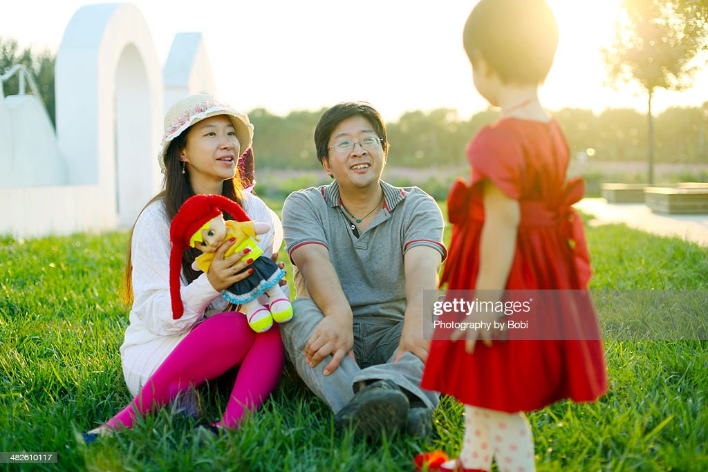 young parents playing with daughter on the grass : Stock Photo