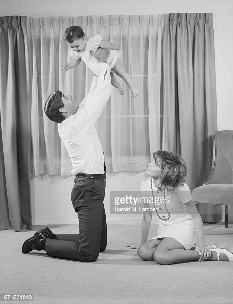 young parents playing with daughter - babyhood stock pictures, royalty-free photos & images