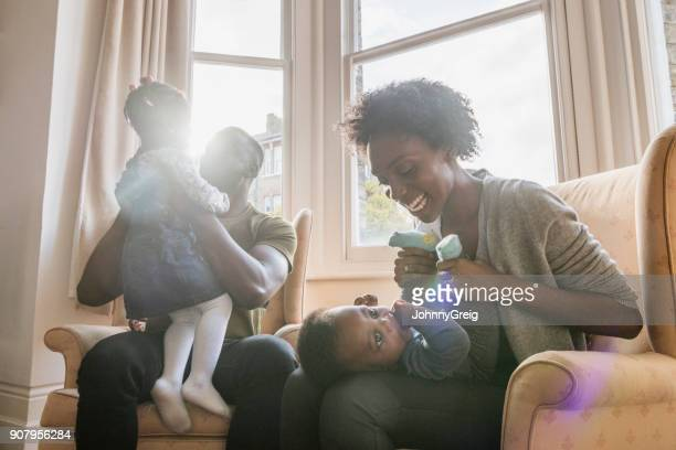 Young parents sitting on armchairs playing with son and daughter