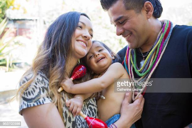 Young parents smiling holding toddler outside in summer