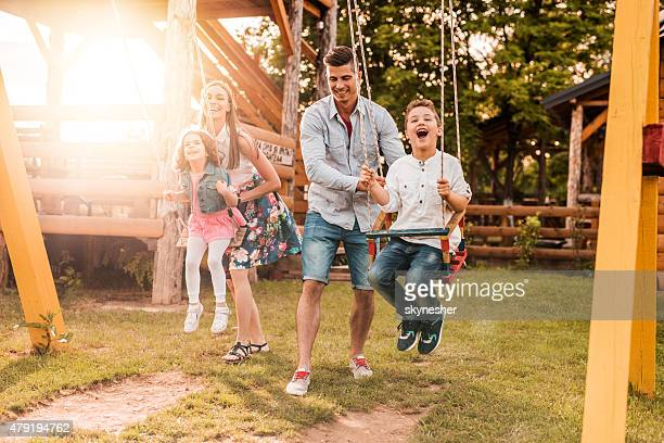 Young parents swinging their cheerful children at sunset.