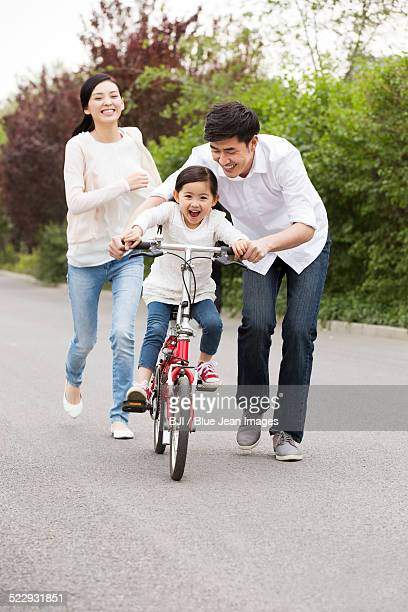 Young parents teaching daughter to ride a bicycle